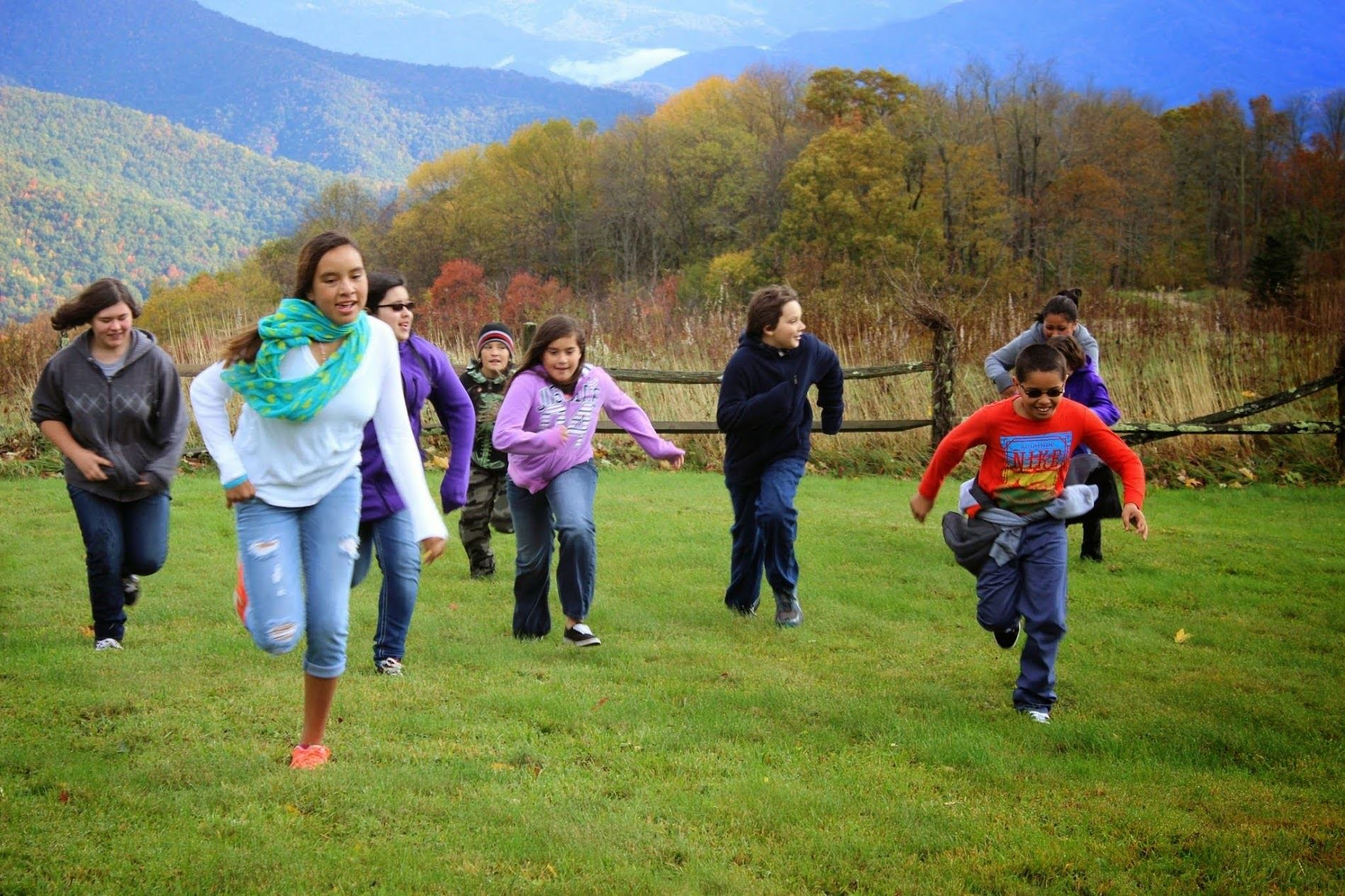 eight middle school aged students running in a field. from left to right: girl in grey sweatshirt with hands in pocket, girl with blue scarf, girl with purple zip up sweatshirt, boy with camouflage sweatsuit, girl with pink sweatshirt, boy with navy pull over, boy with glasses and orange long sleeve shirt and girl with dark hair and grey long sleeve shirt.
