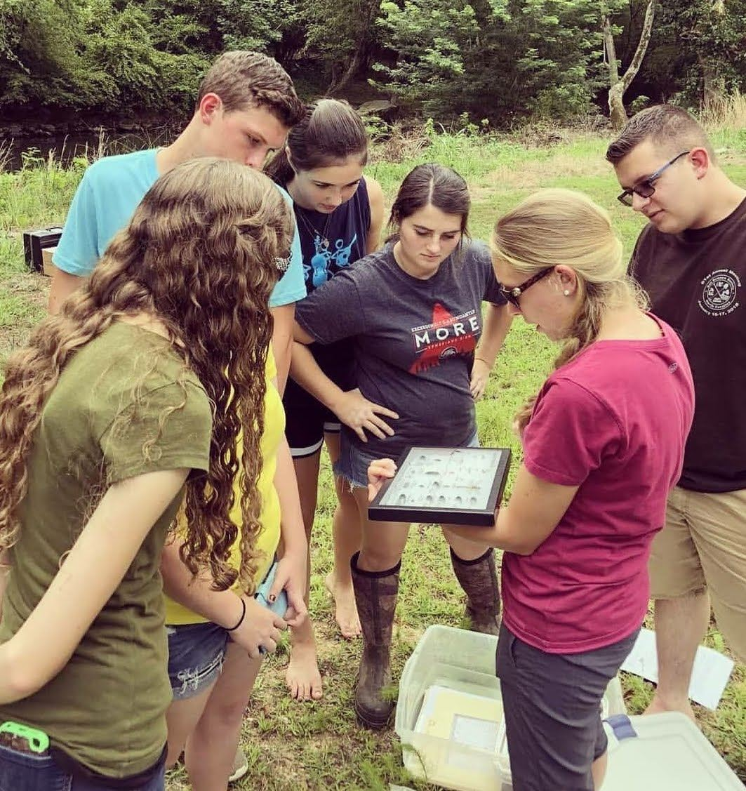 young adult female instructor in magenta shirt leads a group of high school students in envirothon training. There are five students, three girls and two boys, huddled around the instructor looking at an ID sheet.