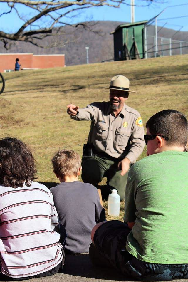 adult male park ranger sitting in a chair (school and baseball field in background) speaking to three young boys.