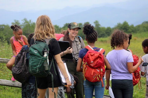 Female park ranger speaking to a group of 7 children with backpacks in front of a field